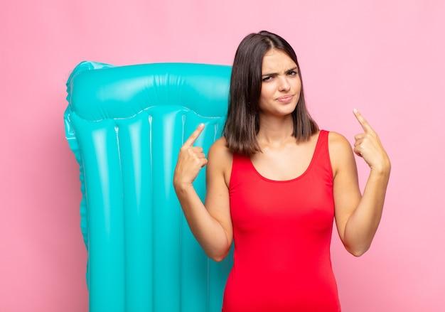 Jeune jolie femme avec une mauvaise attitude semblant fière et agressive, pointant vers le haut ou faisant un signe amusant avec les mains