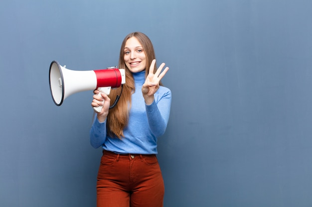 Jeune jolie femme avec un mégaphone contre un mur bleu avec un espace de copie