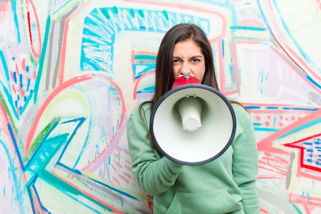 Jeune jolie femme avec un mégaphone contre le mur de graffitis