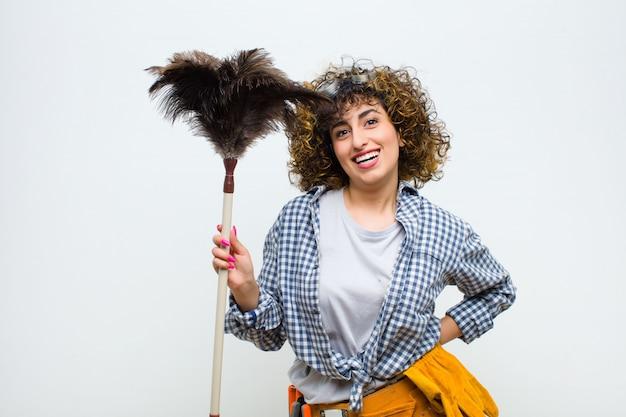 Jeune jolie femme de ménage avec un plumeau