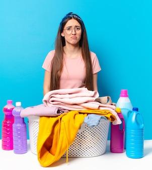 Jeune jolie femme de ménage se sentant triste et pleurnichard avec un regard malheureux, pleurant avec une attitude négative et frustrée