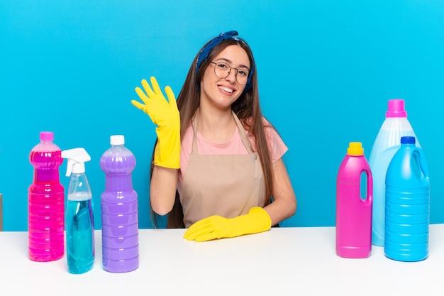 Jeune jolie femme de ménage souriant joyeusement et joyeusement, agitant la main, vous accueillant et vous saluant, ou vous disant au revoir