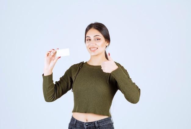 Jeune jolie femme montrant une carte de visite vierge et donnant le pouce vers le haut.