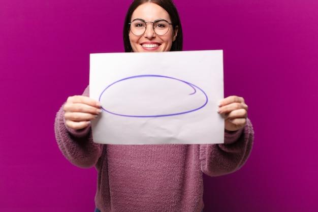 Jeune jolie femme montrant une feuille de papier de remarque