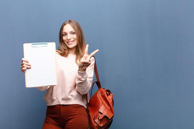 Jeune jolie femme avec un morceau de papier contre le mur bleu avec un espace de copie