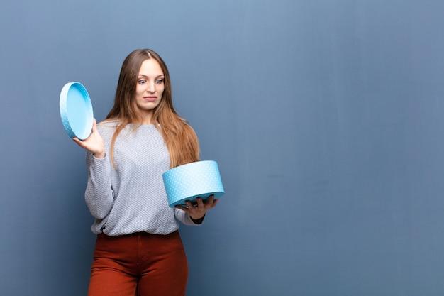 Jeune jolie femme avec un mur bleu boîte bleue avec un fond