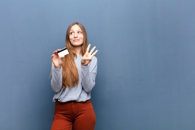 Jeune jolie femme avec un mur bleu de carte de crédit avec un fond