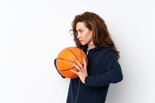 Jeune jolie femme sur un mur isolé avec ballon de basket