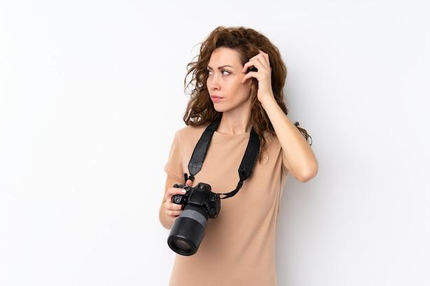 Jeune jolie femme sur un mur isolé avec une caméra professionnelle et pensant