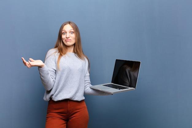 Jeune jolie femme avec un mur d'ordinateur portable bleu avec un espace de copie