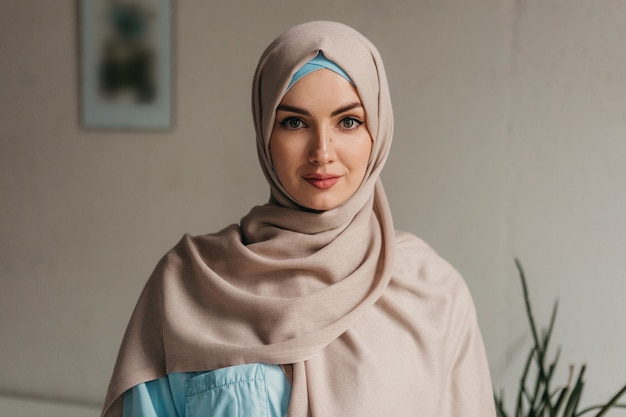 Jeune jolie femme musulmane en hijab travaillant sur un ordinateur portable dans une salle de bureau, éducation en ligne