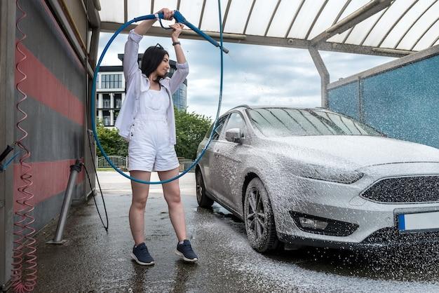 Jeune jolie femme nettoie les roues de voiture avec un pistolet à mousse. lavage automatique