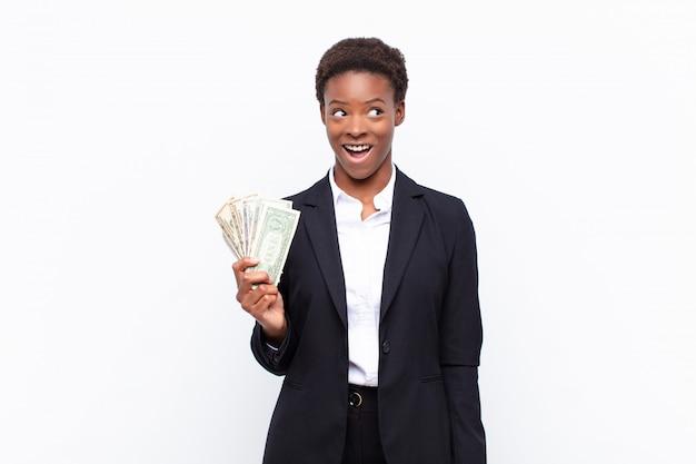Jeune jolie femme noire à l'air heureuse et agréablement surprise, excitée par une expression fascinée et choquée avec des billets en dollars