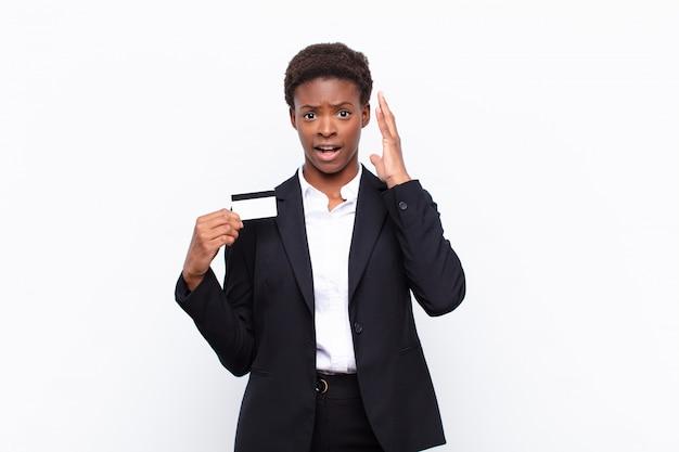 Jeune jolie femme noire criant avec les mains en l'air, se sentant furieuse, frustrée, stressée et bouleversée tenant une carte de crédit