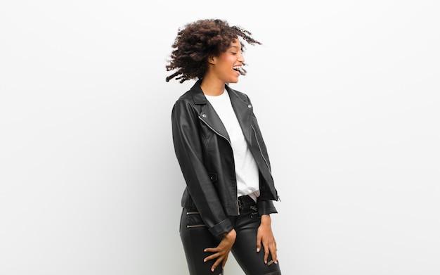 Jeune jolie femme noire dansant vêtue d'une veste en cuir contre un mur blanc