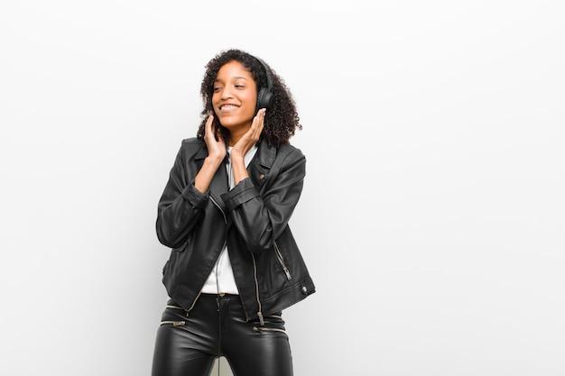 Jeune jolie femme noire écoute de la musique avec un casque portant une veste en cuir contre un mur blanc