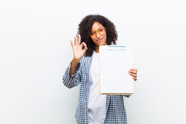 Jeune jolie femme noire avec une feuille de papier contre un mur blanc