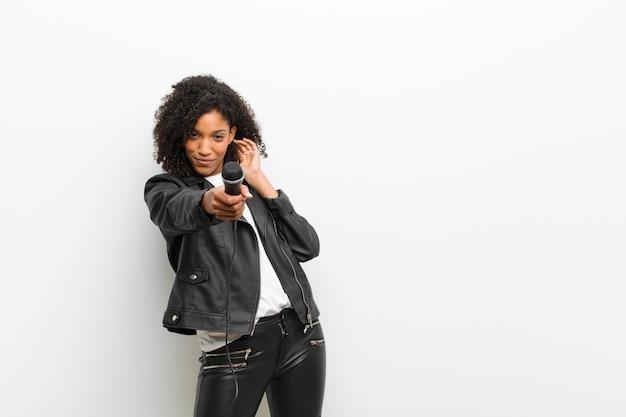 Jeune jolie femme noire avec un microphone portant un mur blanc de veste en cuir