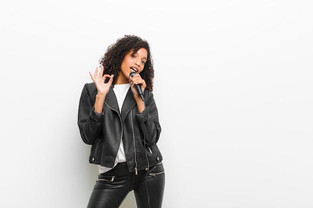 Jeune jolie femme noire avec un microphone portant une veste en cuir contre un mur blanc