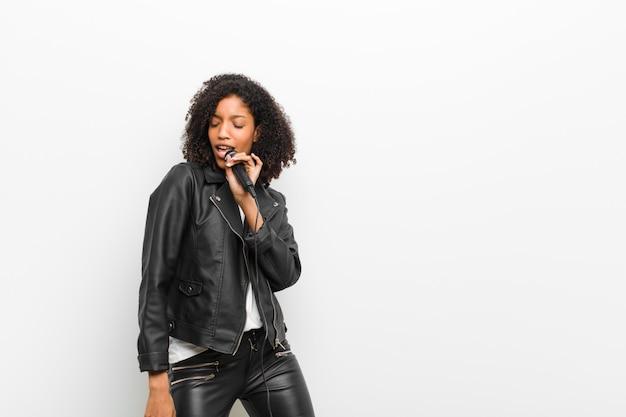 Jeune jolie femme noire avec un microphone portant une veste en cuir