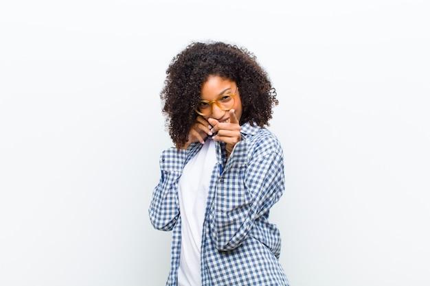 Jeune jolie femme noire avec un mur de téléphone intelligent blanc