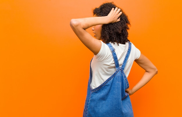 Jeune jolie femme noire pensant ou doutant, se grattant la tête, se sentant perplexe et confus, vue arrière ou arrière contre le mur orange