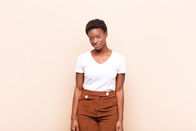 Jeune jolie femme noire à la recherche de plaisir et de convivialité, souriant et vous faisant un clin d'œil avec une attitude positive