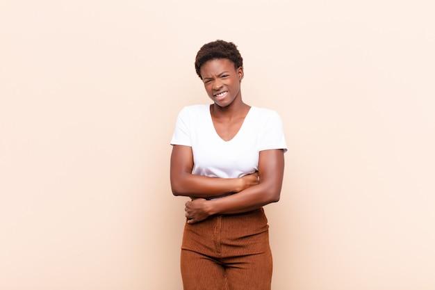 Jeune jolie femme noire se sentant anxieuse, malade, malade et malheureuse, souffrant de maux d'estomac ou de grippe douloureux