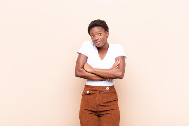 Jeune jolie femme noire, se sentant confuse et incertaine, doutant avec les bras croisés et l'air perplexe