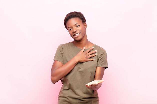 Jeune jolie femme noire se sentant heureuse et amoureuse, souriant d'une main à côté du cœur et de l'autre tendue à l'avant contre le mur rose