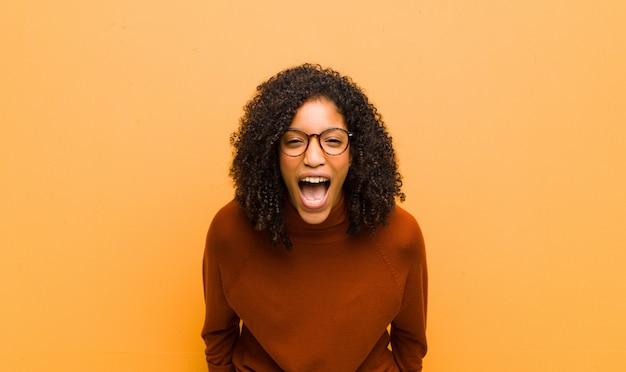 Jeune jolie femme noire se sentant terrifiée et choquée, avec la bouche grande ouverte, surprise contre le mur orange