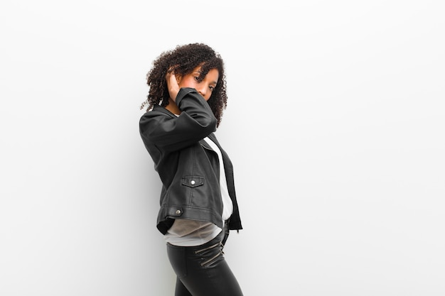 Jeune jolie femme noire vêtue d'un mur blanc de veste en cuir