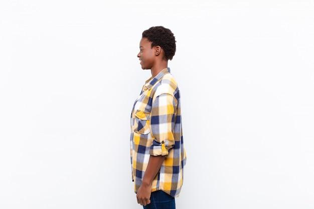 Jeune jolie femme noire vue de profil à la recherche de copier l'espace à venir, penser, imaginer ou rêverie