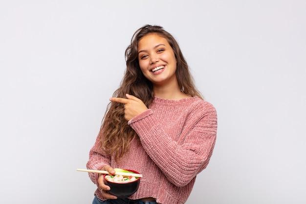 Jeune jolie femme avec des nouilles à l'air excité et surpris pointant vers le côté et vers le haut