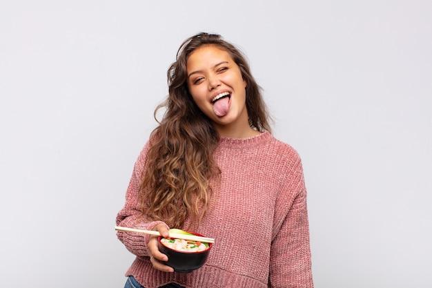 Jeune jolie femme avec des nouilles avec une attitude joyeuse, insouciante et rebelle, plaisantant et collant la langue, s'amusant