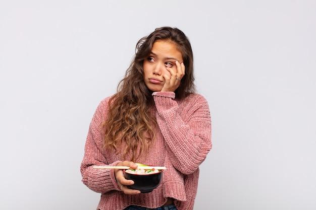 Jeune jolie femme avec des nouilles se sentir ennuyé, frustré et somnolent après une tâche fastidieuse, terne et fastidieuse, tenant le visage avec la main