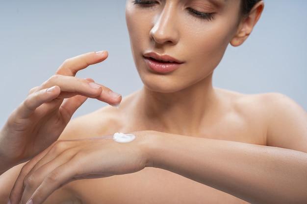 Jeune jolie femme nue à l'aide de crème pour les mains