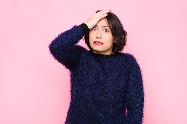 Jeune jolie femme paniquant sur un délai oublié, se sentant stressé, devant couvrir un gâchis ou une erreur sur le mur rose