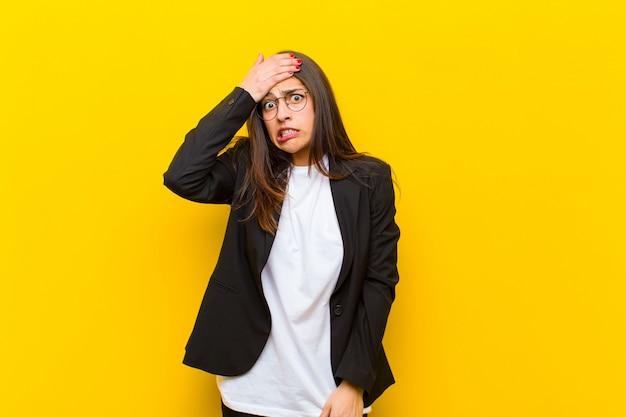 Jeune jolie femme paniquée par une échéance oubliée, se sentant stressée, devant cacher un gâchis ou une erreur contre un mur orange