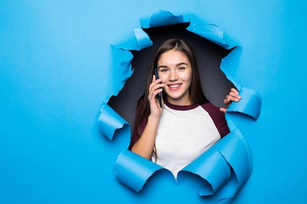 Jeune jolie femme parler téléphone tout en regardant à travers le trou bleu dans le mur de papier.