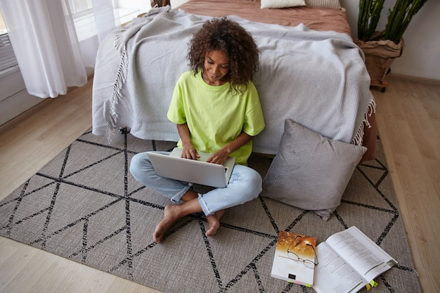 Jeune jolie femme à la peau foncée avec des cheveux bouclés bruns s'appuyant sur le lit dans la chambre à coucher, faire ses devoirs avec des manuels et un ordinateur portable moderne