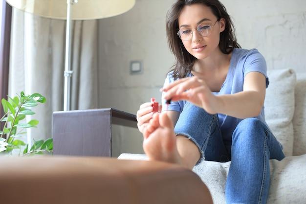 Jeune jolie femme peignant des ongles avec du vernis assis sur un canapé confortable.