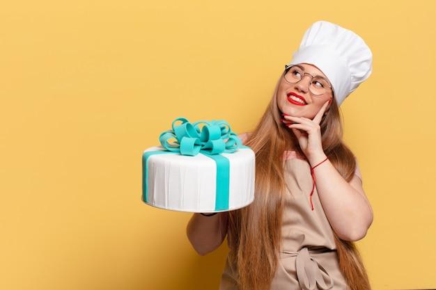 Jeune jolie femme. penser ou douter du concept de gâteau d'anniversaire d'expression