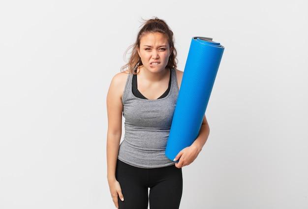Jeune jolie femme à la perplexité et confuse et tenant un tapis de yoga