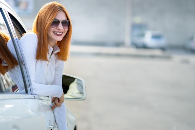 Jeune jolie femme pilote en lunettes de soleil en regardant par la fenêtre avant de la voiture sur une journée d'été ensoleillée.