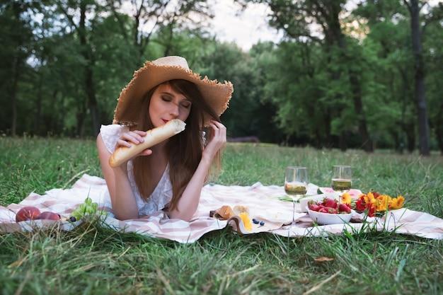 Jeune jolie femme sur un pique-nique dans un parc de la ville