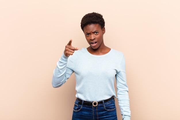 Jeune jolie femme pointant avec une expression agressive en colère ressemblant à un patron furieux et fou