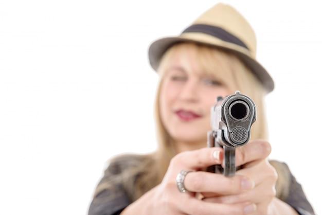 Jeune jolie femme pointant un pistolet sur l'appareil photo avec une main,