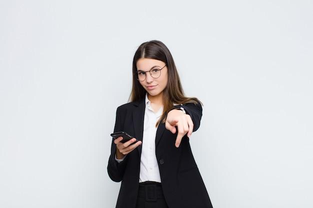 Jeune jolie femme pointant avec un sourire satisfait, confiant et amical, vous choisissant avec un téléphone portable