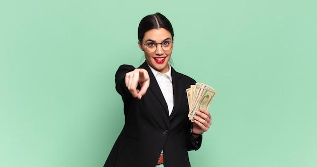 Jeune jolie femme pointant vers la caméra avec un sourire satisfait, confiant et amical, vous choisissant. concept d'entreprise et de billets de banque